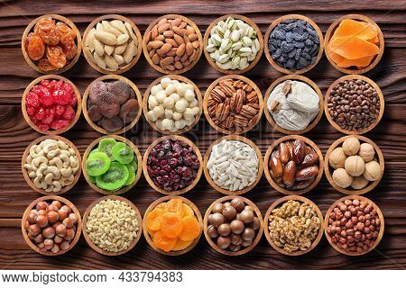 Mix Nuts And Dried Fruits On Table. Raw Food, Nuts In Wooden Bowls, Top View. Assorted Nuts Backgrou