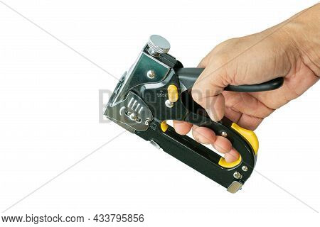 Man Hand Holding A Construction Stapler On A White Background. Heavy-duty Steel Staple Gun To Repair