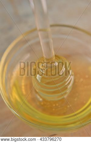 Honey In Glass Jar With Dipper.glass Stick For Honey In A Glass Cup On A Wooden Table. Organic Fresh