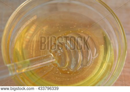 Liquid Honey In Glass Jar With Dipper.glass Stick For Honey In A Glass Cup On A Wooden Table. Organi