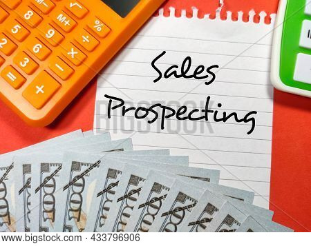 Business Concept.text Sales Prospecting Writing On Notepaper With Fake Money And Calculator On Red B
