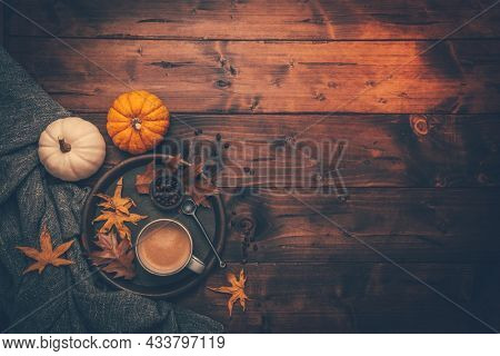 Autumn flatlay with cup of coffee, pumpkins and cuddle blanket on wooden background