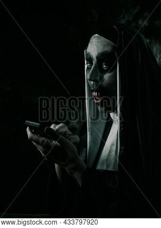 a scary evil nun, with bloody teeth, in a typical black and white habit, uses her smartphone