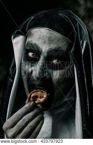 closeup of a scary evil nun eating a human finger with her bloody teeth, wearing a typical black and white habit