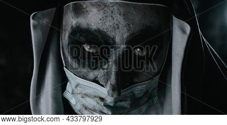 closeup of a scary evil nun, in a typical black and white habit, wearing a dirty disposable face mask