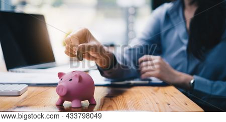 Young Woman Putting A Coin Inside Piggy Bank As Savings For Investment. Wealth And Financial Concept