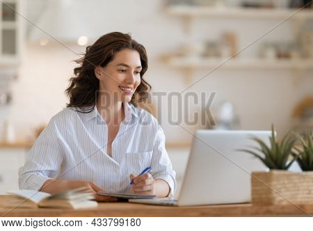 Happy young woman working online, watching webinar, podcast on laptop, having remote conversation at home.