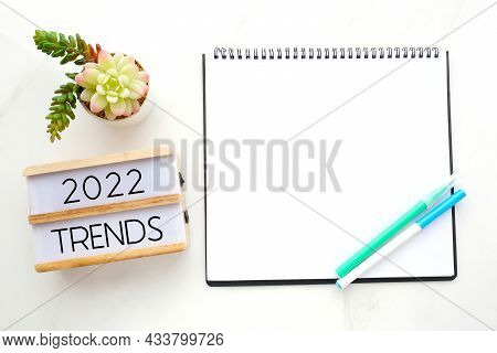 2022 Trends On Wooden Box, Blank Paper Notebook And Pen On White Table Background, New Year Business
