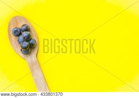 Flat Lay Of Recycled Spoon And Juicy, Fresh Blueberries On Color Table. Space For Text. Isolated Rip