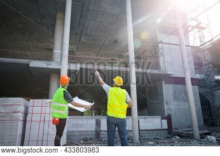 Engineer Discussing With Foreman About Project In Building Construction Site.