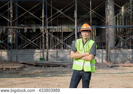Successful Male Architect, Engineer Or Contractor At A Building Site With Arms Crossed. Young Busine