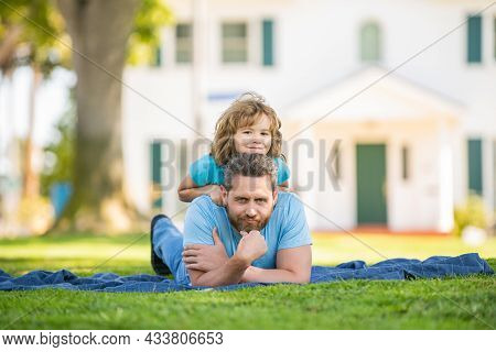 Parent Relax With Little Child Boy On Grass. Dad With Kid On Summer Day. Parenting
