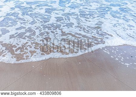 Soft Wave Of The Sea On Sandy Beach White Foam.top View Of A Wave Breaking On The Sand At The Beach.