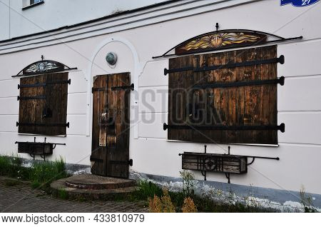 Wooden Door And Shutters On The Windows Of The House. Shutters With Large Metal Hinges.