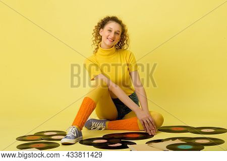 Happy Girl Sitting On Floor With Vinyl Records. Portrait Of Happy Girl With Curly Hairstyle Wearing