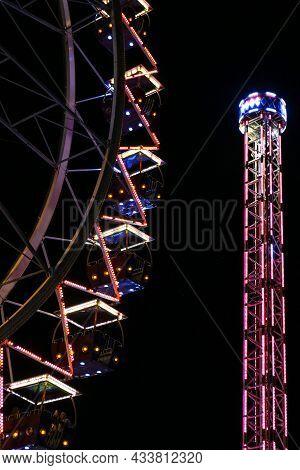 Ferris Wheel Lights At Night. Neon Colored Lights Flashing On The Ferris Wheel. Amusement Park At Ni