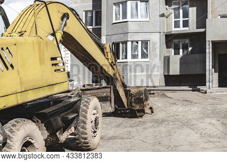 A Heavy Crawler Excavator With A Large Bucket Is Getting Ready For Work In Front Of A Panel House Un