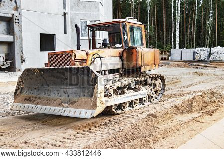 Bulldozer Machine Is Leveling Construction Site. Earthmover With Caterpillar Is Moving Earth. Close-