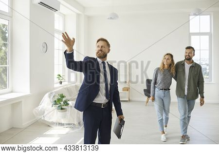 Real Estate Agent Giving Happy Young Customers A Tour About A New Spacious House