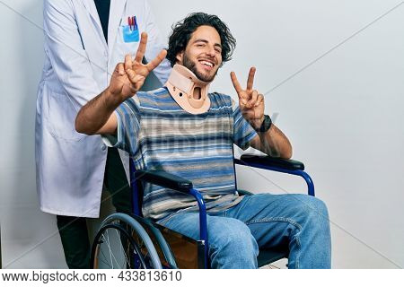 Handsome hispanic man sitting on wheelchair wearing neck collar smiling looking to the camera showing fingers doing victory sign. number two.