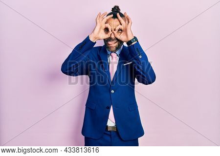 Young hispanic man wearing business suit and tie doing ok gesture like binoculars sticking tongue out, eyes looking through fingers. crazy expression.