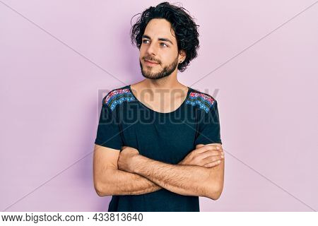 Handsome hispanic man with arms crossed gesture smiling looking to the side and staring away thinking.
