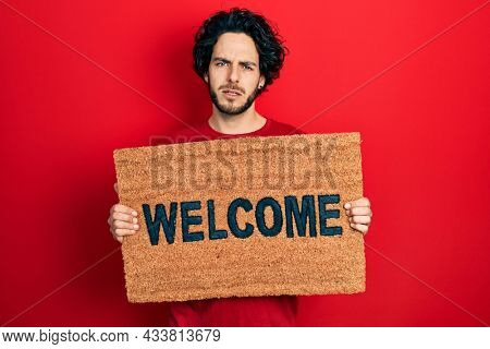 Handsome hispanic man holding welcome doormat clueless and confused expression. doubt concept.