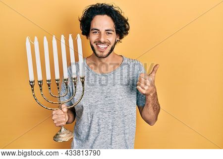 Handsome hispanic man holding menorah hanukkah jewish candle smiling happy and positive, thumb up doing excellent and approval sign