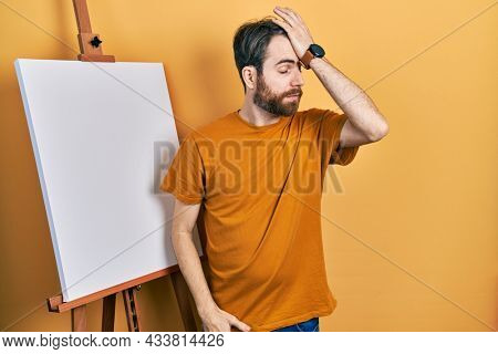 Caucasian man with beard standing by painter easel stand surprised with hand on head for mistake, remember error. forgot, bad memory concept.