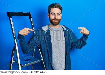 Caucasian man with beard by ladder looking confident with smile on face, pointing oneself with fingers proud and happy.