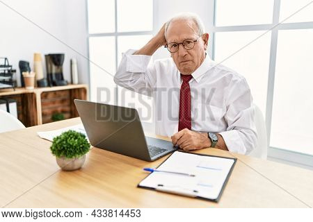 Senior man working at the office using computer laptop confuse and wondering about question. uncertain with doubt, thinking with hand on head. pensive concept.