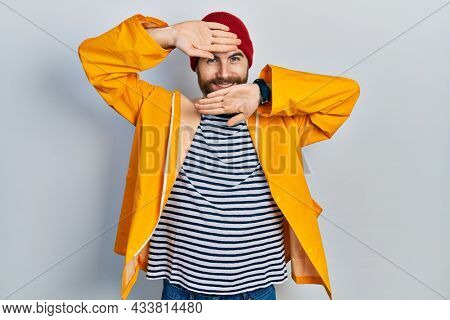 Caucasian man with beard wearing yellow raincoat smiling cheerful playing peek a boo with hands showing face. surprised and exited