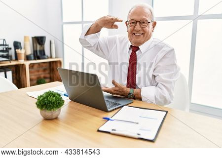 Senior man working at the office using computer laptop gesturing with hands showing big and large size sign, measure symbol. smiling looking at the camera. measuring concept.