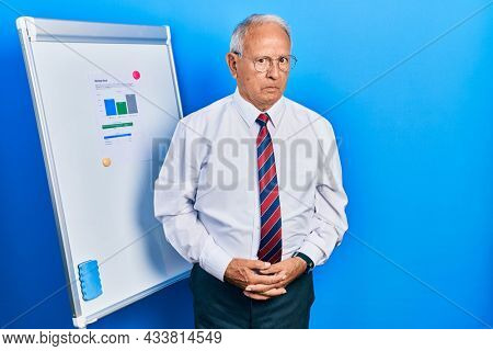 Senior man with grey hair standing by business blackboard skeptic and nervous, frowning upset because of problem. negative person.