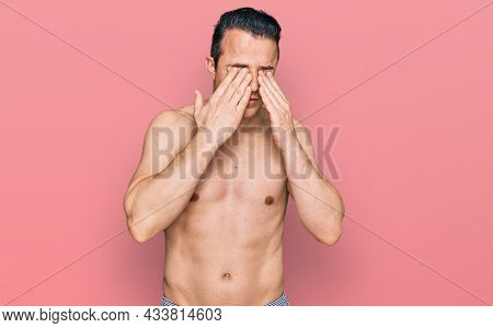 Handsome young man wearing swimwear shirtless rubbing eyes for fatigue and headache, sleepy and tired expression. vision problem