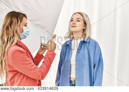 Stylist woman applying make up to beautiful caucasian model at photo shoot backstage, getting ready for professional photoshoot