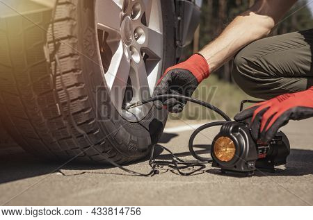 Tire Pump Inflating Car Wheel. Tyre Inflator In Man Hands With Manometer.