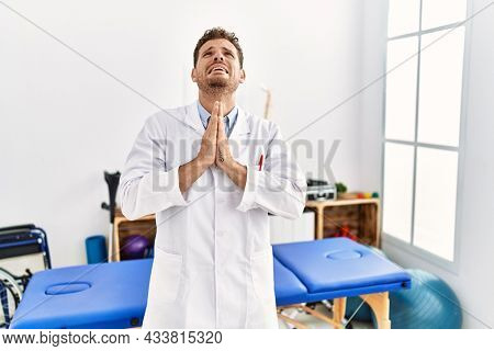 Handsome young man working at pain recovery clinic begging and praying with hands together with hope expression on face very emotional and worried. begging.
