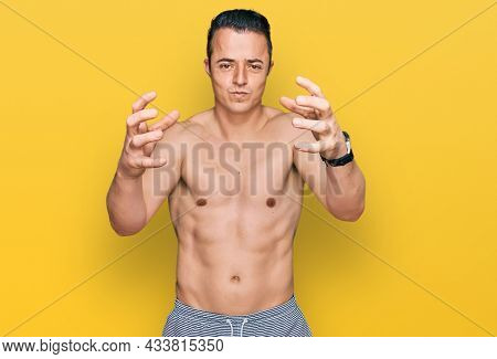 Handsome young man wearing swimwear shirtless shouting frustrated with rage, hands trying to strangle, yelling mad