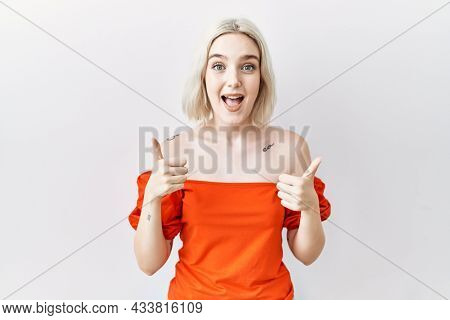 Young caucasian woman standing over isolated background success sign doing positive gesture with hand, thumbs up smiling and happy. cheerful expression and winner gesture.