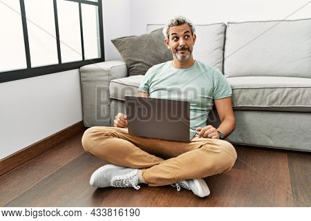 Middle age hispanic man using laptop sitting on the floor at the living room smiling looking to the side and staring away thinking.
