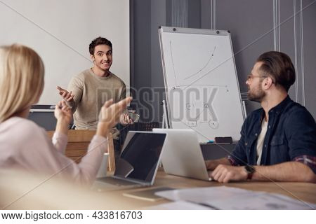 Leader showing business graph on interactive board to colleagues. Concept of successful people. Idea of business and entrepreneur lifestyle. European men and woman are discussing. Office interior