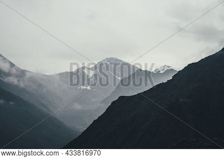 Dark Atmospheric Landscape With Black Mountains Silhouettes Among Rainy Low Clouds. Gloomy Mountain