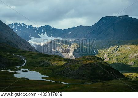 Atmospheric Alpine Landscape With Mountain Lake In Green Valley And Glacier Under Cloudy Sky. Awesom