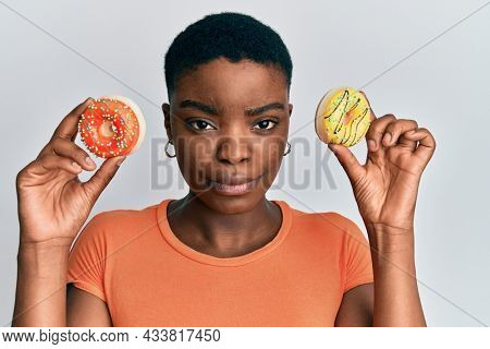Young african american woman holding tasty colorful doughnuts on eyes skeptic and nervous, frowning upset because of problem. negative person.