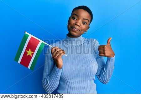 Young african american woman holding suriname flag smiling happy and positive, thumb up doing excellent and approval sign
