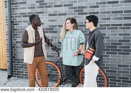 Modern African American Guy And His Female Co-workers Standing Together Outdoors Talking About Somet