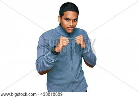 Young handsome hispanic man wearing casual sweatshirt ready to fight with fist defense gesture, angry and upset face, afraid of problem