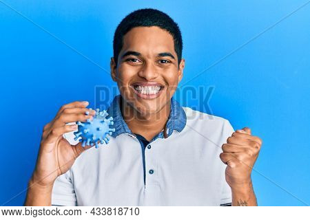 Young handsome hispanic man holding virus toy screaming proud, celebrating victory and success very excited with raised arm