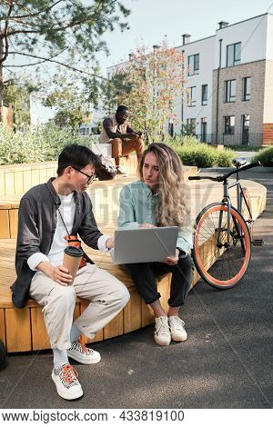 Vertical Shot Of Two Young Co-workers Spending Time Outdoors Sitting In Modern Park Looking At Somet